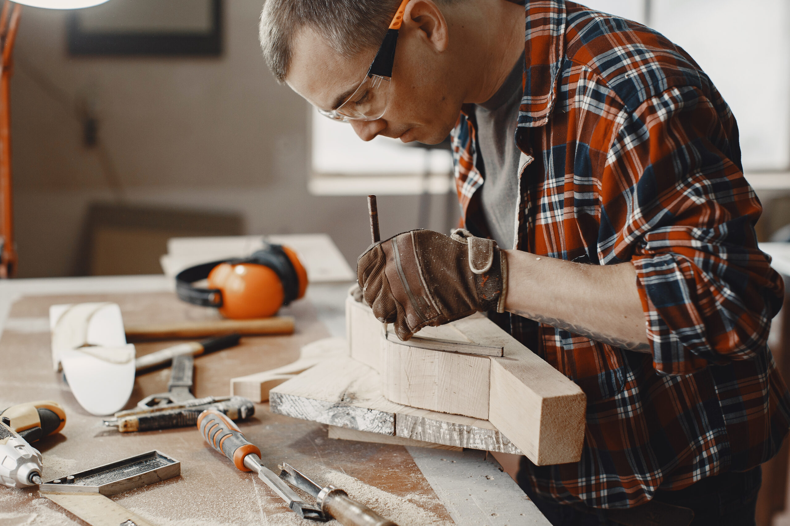 Craftsman cutting a wooden plank. Worker with wood. Man in a cell shirt.